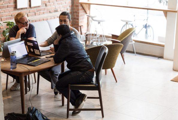 Ansatte sitter rundt et bord og diskuterer