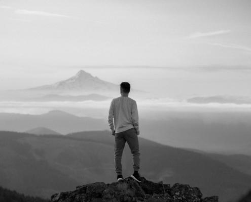 Svart hvitt bilde av en mann som ser ut over landskap