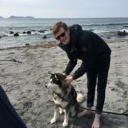 Mann på stranden med hunden sin