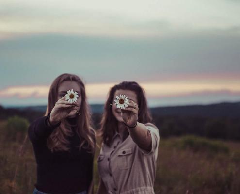 To kvinner gjemmer seg bak blomster på et jorde
